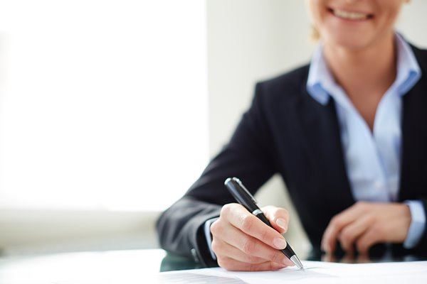 Image of female hand signing document at workplace